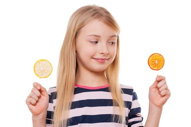 어려운 선택. 흰색으로 격리된 채 손에 막대 사탕을 들고 웃고 있는 쾌활한 어린 소녀