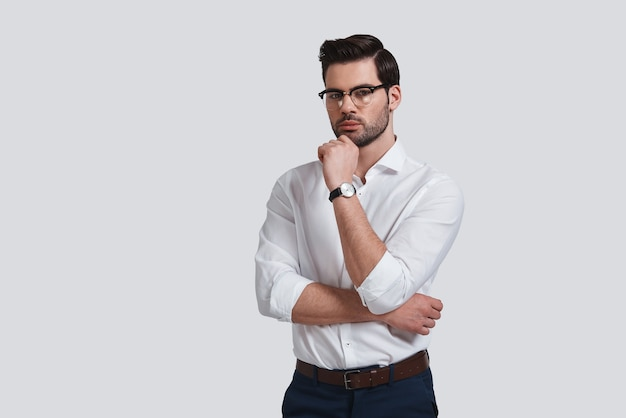 Hard choice. good looking young man in formalwear keeping hand on chin and looking at camera while standing against grey background