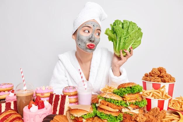 어려운 선택. 진지한 슬픈 여성은 로메인 상추를 들고 건강한 음식과 건강에 해로운 음식 사이에서 선택하려고 하며 맛있는 햄버거 감자튀김과 케이크를 먹고 싶은 유혹을 느낍니다 무료 사진