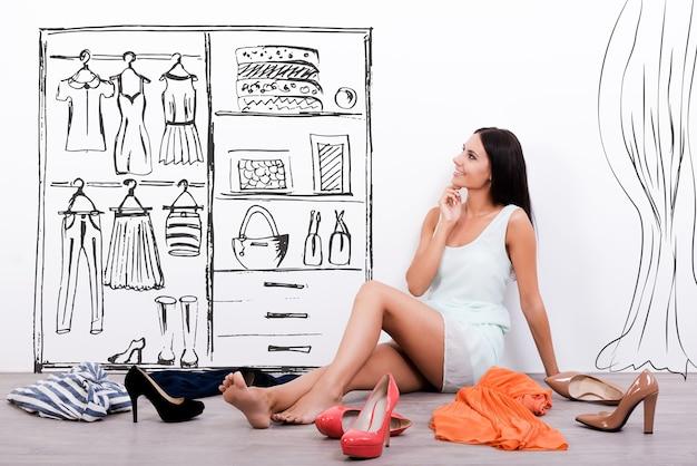 어려운 선택. 드레스를 입은 사려깊은 젊은 여성이 옷과 신발을 둘러싸고 바닥에 앉아 벽에 있는 스케치를 보고 있다