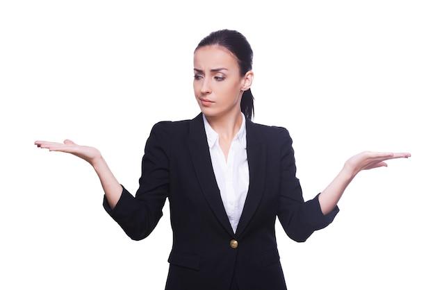 어려운 선택. 흰색에 고립 된 서있는 동안 두 손에 복사 공간을 들고 formalwear에서 사려 깊은 젊은 여자