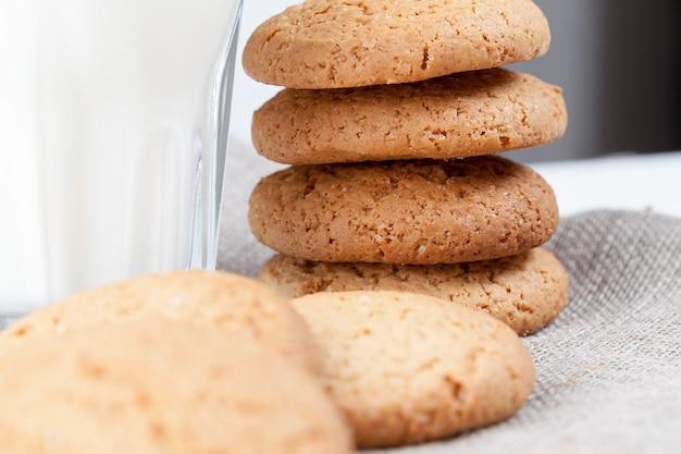 オートミールと小麦粉で焼いたハードクッキー、甘くないが砂糖を加えたドライでカリカリのクッキー、テーブルの上の低カロリーオートミールクッキー、白い新鮮な牛乳のグラス