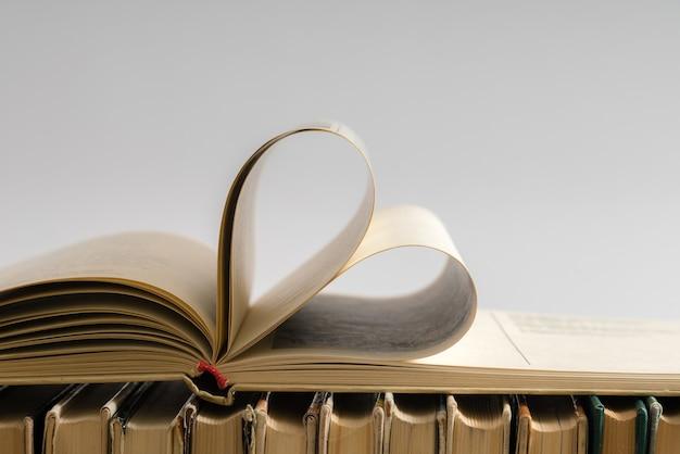 バレンタインデーの愛のためにハートの形に飾られたハードカバーの本のページ