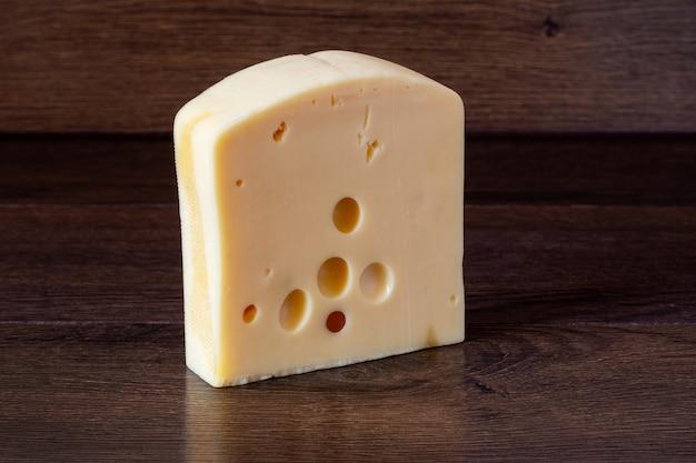 Твердый сливочный сыр на темном деревянном фоне. вкусная и здоровая еда