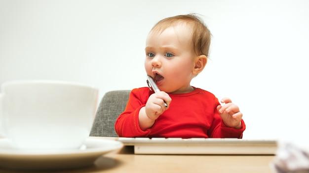ハードな日。現代のコンピューターのキーボードまたは白いスタジオのラップトップで座っている子女の赤ちゃん