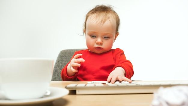 힘든 날. 흰색 스튜디오에서 현대 컴퓨터 또는 노트북의 키보드와 함께 앉아 아이 아기 소녀