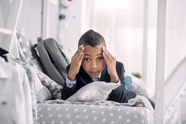 힘든 날. 그의 사원을 만지고있는 동안 침대에 누워 불안한 아프리카 계 미국인 소년