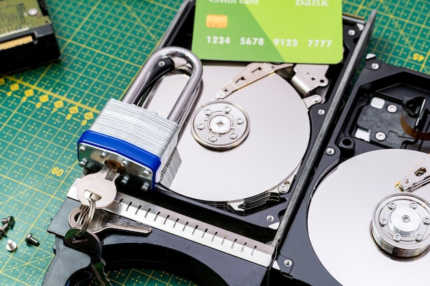 Hard disk drive with credit card and lock. ransomware virus, data protection concept