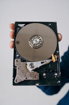 회색 공간에서 남자의 손에 분해 된 하드 드라이브