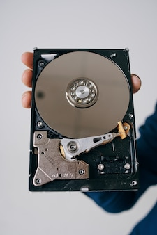 Hard drive disassembled in a man's hand on a gray space