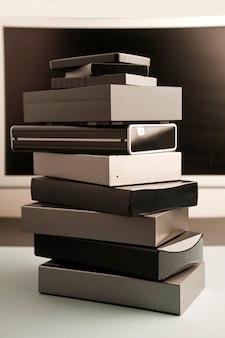 Стек жестких дисков разных размеров и разных цветов с частичным видом на компьютер и белым фоном