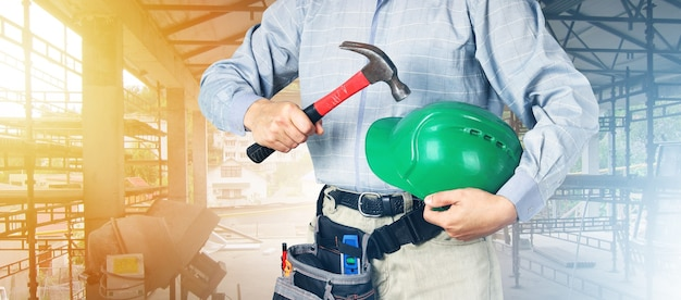 Hard hat and hammer in hands of builder, safety concept