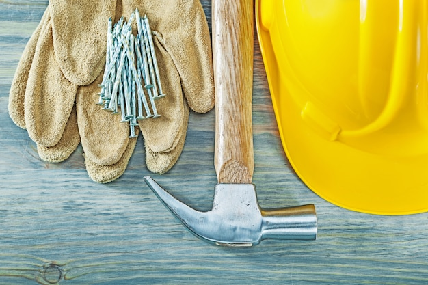 Hard hat protective gloves claw hammer nails on wooden board construction concept