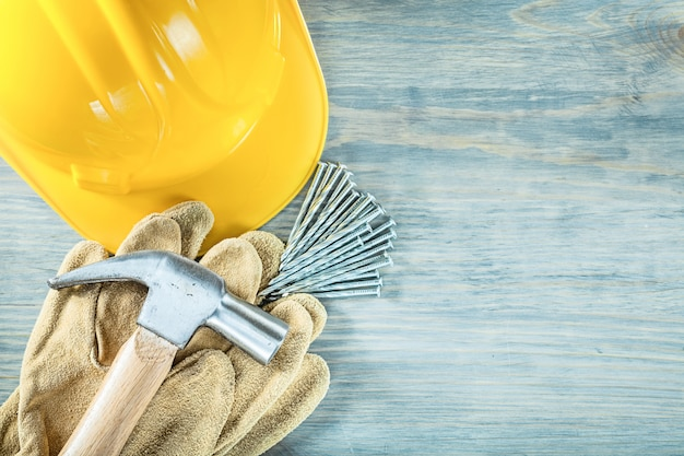 Hard hat safety gloves claw hammer nails on wooden board construction concept