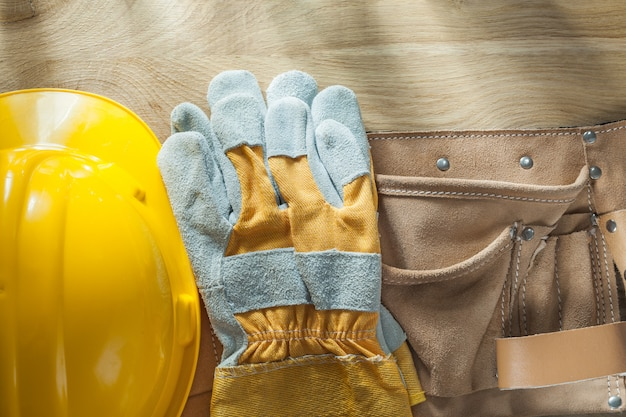Hard hat safety gloves leather construction belt on wooden board