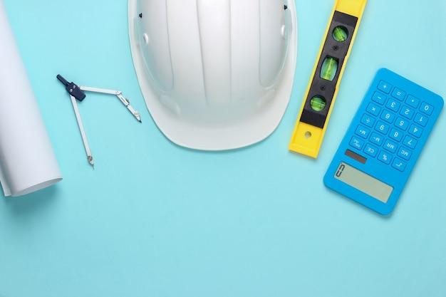 建物のレベル、電卓、コンパス、青いスタジオの青写真とヘルメット
