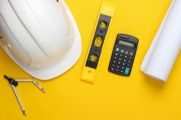 建物のレベル、電卓、コンパス、黄色のスタジオの青写真とヘルメット