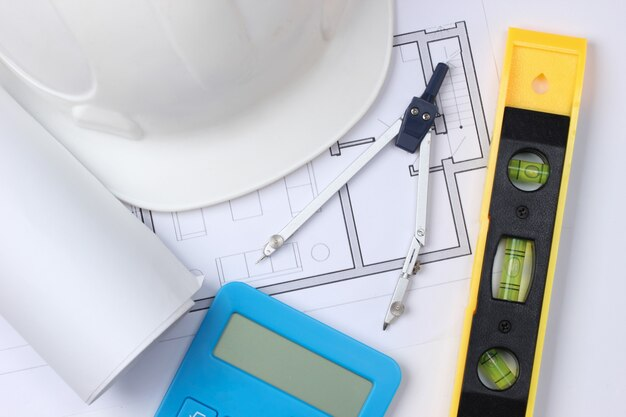 建物レベル、電卓、コンパス、青写真付きのヘルメット