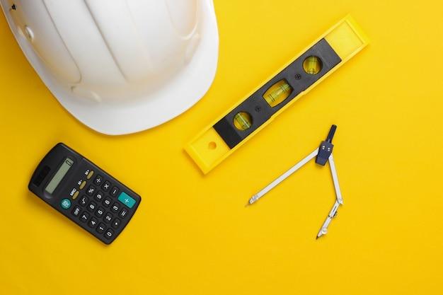 建物のレベル、電卓、黄色のスタジオのコンパスとヘルメット