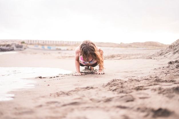 Жесткое положение планки на берегу у океанских волн. приятные занятия спортом на свежем воздухе в контакте с природой и песком. тело здоровья для красивой красивой молодой женщины оставаться хорошо с фитнесом. центральное положение
