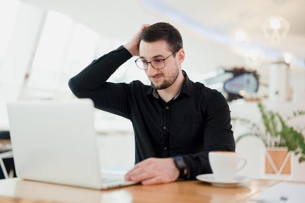ハードリモートワーク。頭を抱えているフリーランサーの男性は、雇用主とのチャットで何が起こっているのか理解していません。喫茶店で働いていて、ラップトップを使用している黒いシャツを着た男性のリモートワーカー。
