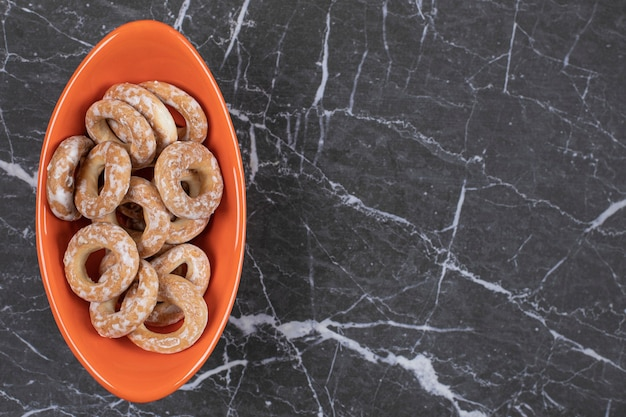 Hard salted pretzels in orange bowl.