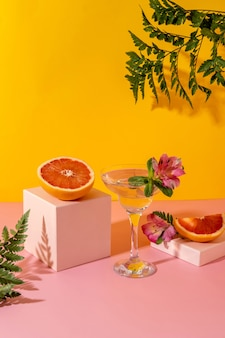Крепкий зельтерский коктейль с ягодным вкусом, украшенный цветком альстромерии. освежающий красочный летний напиток на желтом фоне с тенью папоротника.
