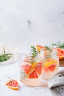 Коктейль с твердым зельтером с грейпфрутом, розмарином и льдом на столе. летний освежающий напиток, напиток на белом столе