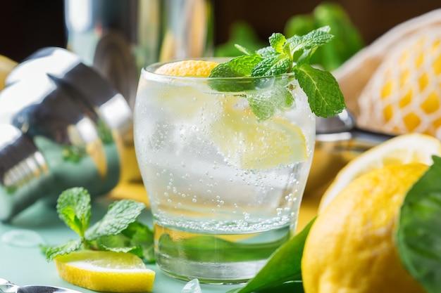 Коктейль с твердым зельтером с лимоном, мятой и льдом на столе. летний освежающий напиток, напиток с модными аксессуарами без отходов, бамбуковой соломкой и сетчатым мешком.