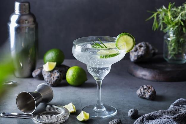 Крепкий зельтер-коктейль с лаймом, розмарином и льдом на столе. летний освежающий напиток, напиток