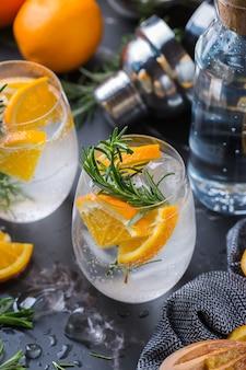 Крепкий зельтер-коктейль с апельсином, розмарином и льдом на столе. летний освежающий напиток, напиток на черном столе