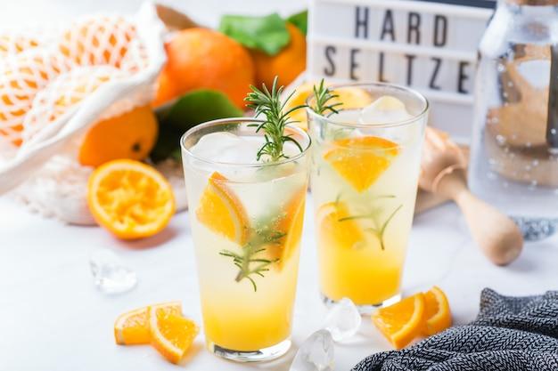 Крепкий зельтер-коктейль с апельсином, розмарином и льдом на столе. летний освежающий напиток, напиток на белом столе