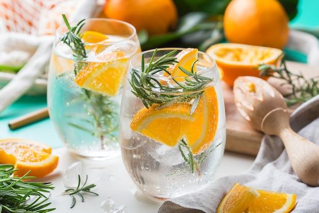 Крепкий зельтер-коктейль с апельсином, розмарином и льдом на столе. летний освежающий напиток, напиток с модными аксессуарами без отходов, бамбуковой соломкой и сетчатым мешком.