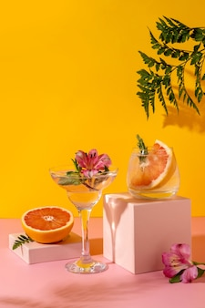 Коктейли с твердым зельтером с ягодным вкусом, украшенные цветком альстромерии. освежающий красочный летний напиток на желтом фоне с тенью папоротника.