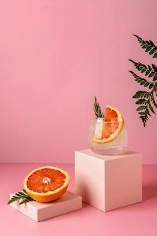 Крепкие зельтер-коктейли с грейпфрутом и розмарином. освежающий красочный летний напиток на розовом фоне с листьями папоротника.