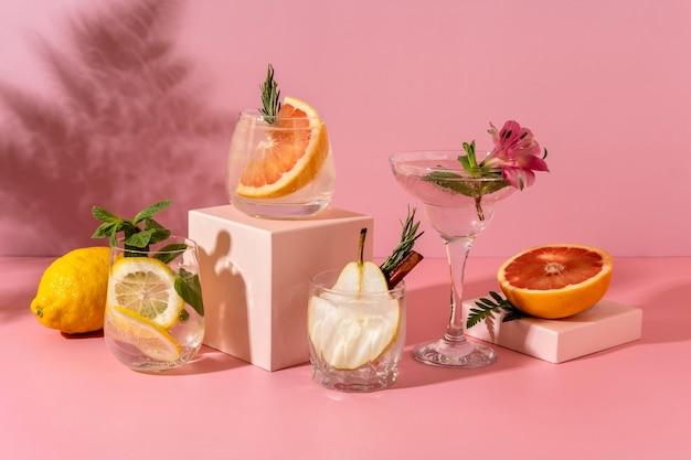 洋ナシ、グレープフルーツ、レモンなど、さまざまなフルーツを使ったハードセルツァーカクテル。影のシダとピンクの背景にさわやかなカラフルな夏の飲み物。