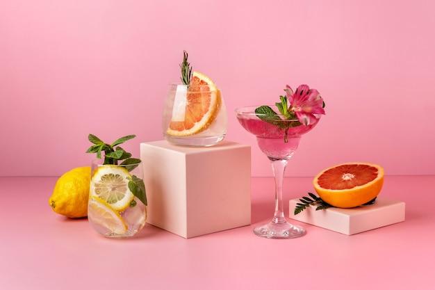 배, 자몽, 레몬 등 다양한 과일이 들어간 하드 셀처 칵테일. 분홍색 배경에 상쾌한 화려한 여름 음료