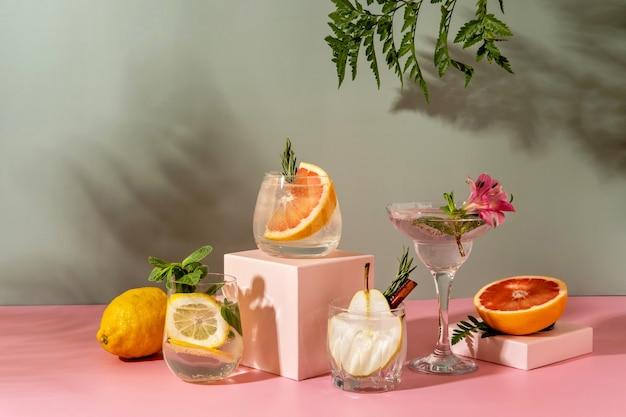 洋ナシ、グレープフルーツ、レモンなど、さまざまなフルーツを使ったハードセルツァーカクテル。影のシダと黄色の背景にさわやかなカラフルな夏の飲み物。