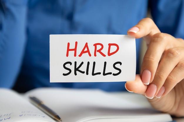 На белой визитной карточке в женской руке написано «твердые навыки». синий фон. бизнес и рекламная концепция