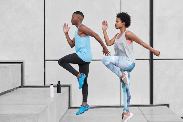 ハードスポーツのコンセプト。 2つの黒い女性と男性の駆け上がりのステップのモーションショットは、高く登る優れた能力を示し、脱水を防ぐために真水が入ったボトルを持ち、白い壁に向かって移動します