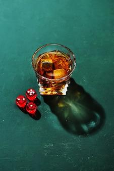 ガラスとカジノのダイスの硬い強いアルコール飲料:コニャック、テキーラ、スコッチ、ブランデー、またはウイスキー、緑の背景にハードライトとシャドウ、上面図。
