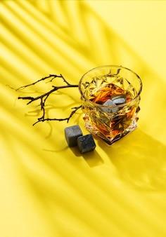 ガラスの硬い強いアルコール飲料:コニャック、テキーラ、スコッチ、ブランデー、またはウイスキー、黄色の背景に硬い光と影、上面図