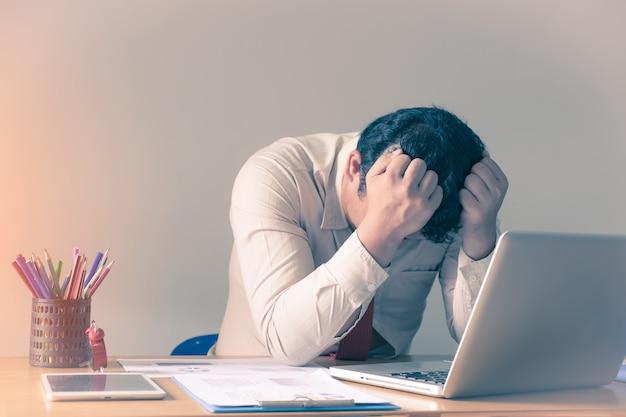 Трудно думать об анализе в работе. подчеркнутый молодой бизнесмен в офисе