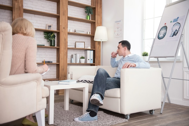 Hard times. melancholy upset man sitting during therapy while turning aside