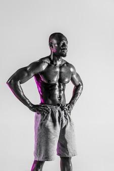 ハードワークは常に報われます。灰色の背景の上の若いアフリカ系アメリカ人のボディービルダーのトレーニング。スポーツウェアに立っている筋肉の単一の男性モデル。スポーツ、ボディービル、健康的なライフスタイルの概念。