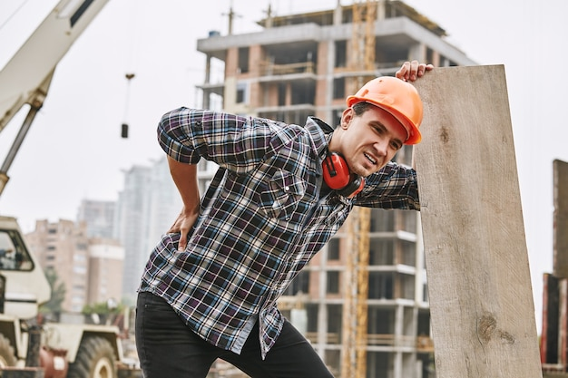 建設作業中に背中の痛みを感じる保護ヘルメットの勤勉な建設労働者