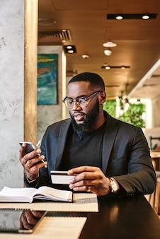 ハードワークは、モバイルとクレジットカードを保持しているアフリカ系アメリカ人のビジネスマンのショットを完済します