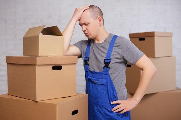 힘든 일, 두통, 스트레스 개념 - 큰 판지 상자 사이의 피곤한 로더 또는 배달원