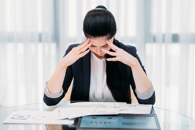 사무실에서 힘든 근무. 그녀의 책상에서 피곤 된 비즈니스 우먼