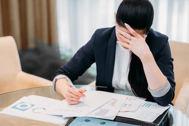 オフィスでのハードワークデイ。彼女の机で疲れたビジネスウーマン